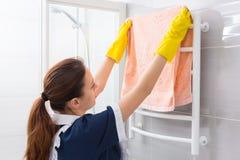 Maid replacing towel on rack in bathroom Royalty Free Stock Photos
