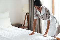 Maid setting up white bed sheet in hotel room Stock Photography