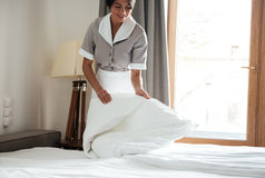Maid setting up white bed sheet in hotel room Stock Image