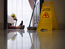 Maid slipped on wet floor and laying down. Housemaid had accident at work while cleaning floor in hotel room. Side view, low angle Stock Photography