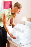 Maid som gör rum som är tjänste- i hotell Arkivbild