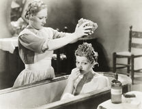 Maid squeezing sponge on woman in bathtub stock photography