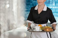 Maid with tray with fruit. Maid holding a tray with fruit, coffee, water and croissants for a hotel guest stock photography