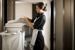 Maid At Work. Maid with housekeeping cart, in hotel royalty free stock images