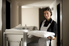 Maid At Work. Maid with housekeeping cart, in hotel stock photo