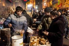 Maidan - activiste donnant la soupe et le pain aux protestataires Images stock