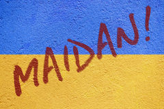 Maidan! incription on Ukraine flag painted on old concrete wall Stock Photos