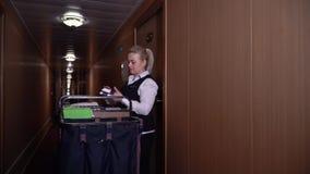 Maide lindo con los paseos de la carretilla en el pasillo del hotel La mujer entra en el cuarto metrajes