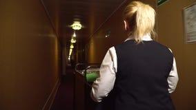 Maide lindo con los paseos de la carretilla a lo largo del pasillo del hotel almacen de metraje de vídeo