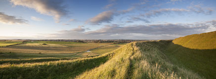Maiden Castle. The late evening sunshine rakes across the Iron Age hill fort of Maiden Castle in Dorset, England. Dorchester, the County Town of Dorset, is royalty free stock photo