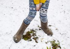 Maiden legs in warm pants and felt boots. The girl in the snow in the winter.  stock photos