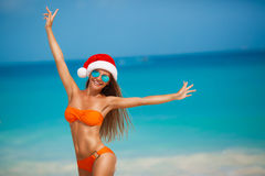 Maiden in orange bikini and hat of Santa Claus Royalty Free Stock Images