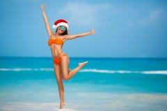 Maiden in orange bikini and hat of Santa Claus Stock Images