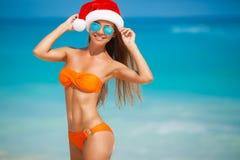 Maiden in orange bikini and hat of Santa Claus Royalty Free Stock Photos