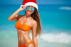Maiden in orange bikini and hat of Santa Claus Royalty Free Stock Photo
