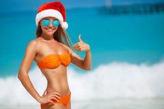 Maiden in orange bikini and hat of Santa Claus Stock Photos
