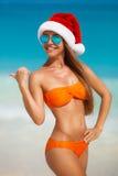 Maiden in orange bikini and hat of Santa Claus Stock Photography