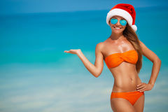 Maiden in orange bikini and hat of Santa Claus Stock Photos