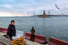 Maiden's Tower in Istanbul, Turkish bagel salesman. Istanbul, Turkey - December 04, 2013: A pretzel vendor and a man feeding seagulls appear Royalty Free Stock Photo