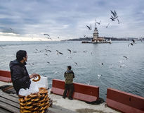 Maiden's Tower in Istanbul, Turkish bagel salesman. Istanbul, Turkey - December 04, 2013: A pretzel vendor and a man feeding seagulls appear Stock Photography