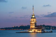 Maiden's Tower. Lit up in early evening, with the Hagia Sophia and the Blue Mosque in the far distance Royalty Free Stock Photography