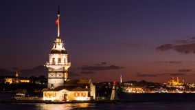 Maiden Tower or Kiz Kulesi with floating tourist boats on Bosphorus in Istanbul at night Royalty Free Stock Image