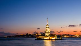 Maiden Tower or Kiz Kulesi with floating tourist boats on Bosphorus in Istanbul at night Stock Photos