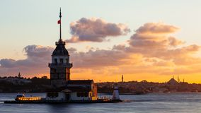 Maiden Tower or Kiz Kulesi with floating tourist boats on Bosphorus in Istanbul at sunset royalty free stock photos