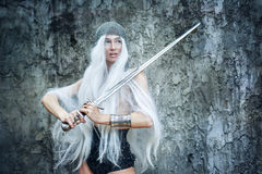 Maiden Warriors. Attractive gray-haired maiden warrior in armor with sword in hand Stock Photo