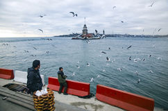 Maidens Tower in Istanbul, Turkish bagel salesman. Istanbul, Turkey - December 04, 2013: A pretzel vendor and a man feeding seagulls appear Stock Photo