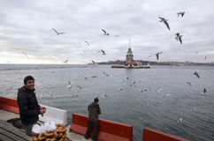 Maidens Tower in Istanbul, Turkish bagel salesman. Istanbul, Turkey - December 04, 2013: A pretzel vendor and a man feeding seagulls appear Stock Photos