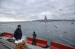 Maidens Tower in Istanbul, Turkish bagel salesman. Istanbul, Turkey - December 04, 2013: A pretzel vendor and a man feeding seagulls appear Royalty Free Stock Photography