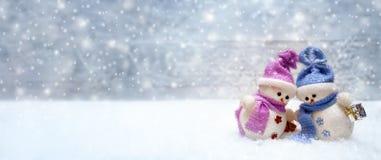 Maigre heureux de couples de bonhommes de neige sur l'un l'autre Photo stock