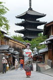 Maiko with Buddish temple on the background, Kyoto. KYOTO, JAPAN - JULY 2: Maiko walking in Kyoto street. Apprentice geisha in Japan. Their jobs consist of Royalty Free Stock Photo