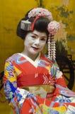 Maiko i röd kimono med guld- bakgrund Fotografering för Bildbyråer