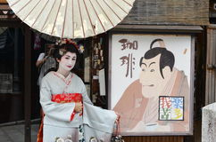 Maiko posing with Japanese poster. KYOTO, JAPAN - JULY 2: Maiko walking in Kyoto street. Apprentice geisha in Japan. Their jobs consist of performing songs Royalty Free Stock Photos
