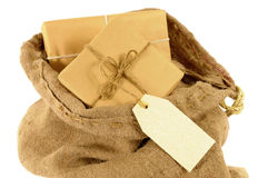 Mail bag or sack with wrapped packages, plain manila label or address tag Stock Photos
