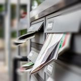 Mail box full of junk mails. Mailbox full of junk of adverstising brochures outside apartment block. Defocused blurry background royalty free stock photo