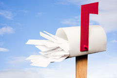Mail box overflowing with mail against sky Stock Photo