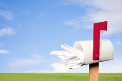 Mail box overflowing with mail against sky Royalty Free Stock Image