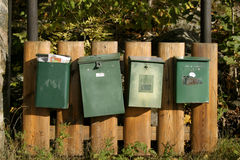 Mail Boxes. A group of mail boxes attached to a wooden fence Royalty Free Stock Images