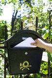 Mail delivery. Mail box delivery, hand and letters next to postal box hanged on iron fence Stock Photos