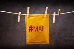 Mail Envelope with hash tag on clothes rope. Predictive shipping concept. Postal mail Envelope with hash tag hanging on rope attached with clothes pins Stock Image
