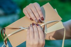 Mail envelope in woman`s hands with red manicure. Outdoor Royalty Free Stock Photos