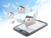 Mail enveloppe with wings on smartphone. Against the sky Royalty Free Stock Photo