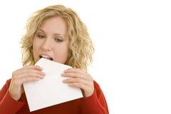 Mail exchange. Blonde woman licking an envelope stock photo