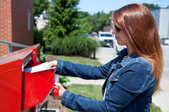 Mail a Letter. A pretty girl puts a letter into the mailbox Stock Photo