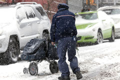 Mail man with carriage during snow storm Stock Images