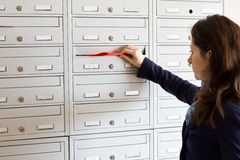 Mail promotion. Woman inserting envelope with mail promotion material in mailboxes Stock Image