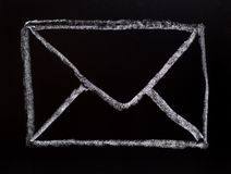 Mail symbol drawn on blackboard Stock Images
